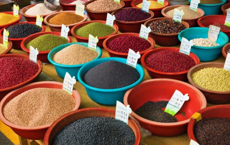 Colourful spices at a spice market each in coloured bowls.